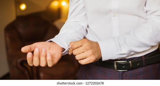 Businessman puts on a white stylish shirt. Button up the sleeves on the shirt