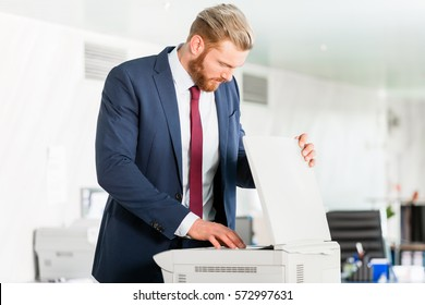 Businessman puts paper in the copying machine