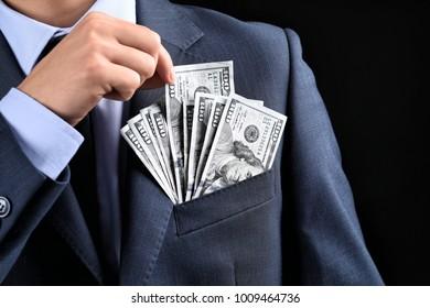 Businessman putting banknotes in pocket on dark background. Corruption concept