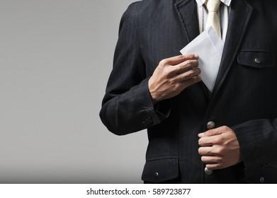 Businessman putting bribe in suit pocket. Corruption concept