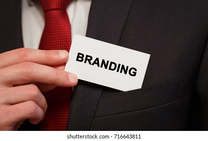 Businessman putting a card with text Branding in the pocket