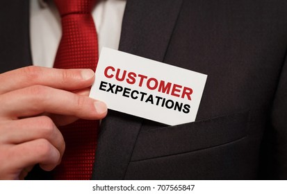Businessman putting a card with text Customer Expectations in the pocket