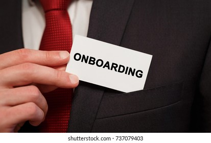 Businessman putting a card with text Onboarding in the pocket