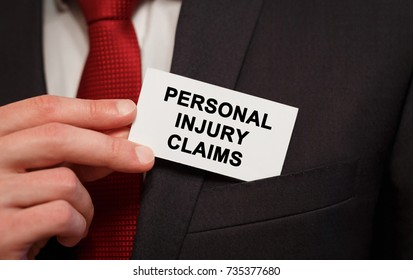 Businessman putting a card with text Personal injury claims in the pocket