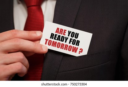 Businessman putting a card with text ARE YOU READY FOR TOMORROW in the pocket