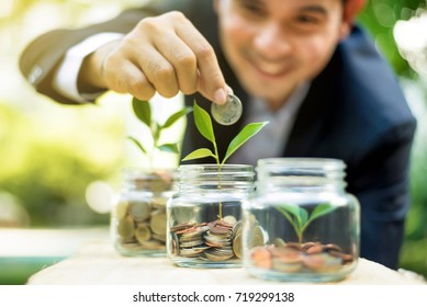 Businessman putting coin into the glass jar with young plant, demonstrating financial growth through saving plans and investment schemes