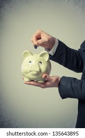 businessman putting a coin into a piggy bank on a gray background