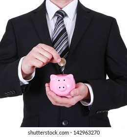 Businessman putting coin into the piggy bank isolated on white background