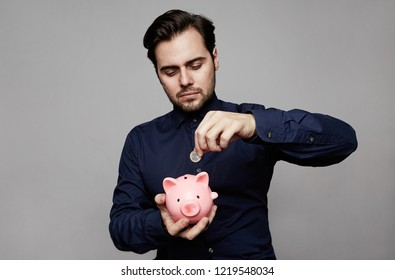 Businessman putting coin into small pink piggy bank.