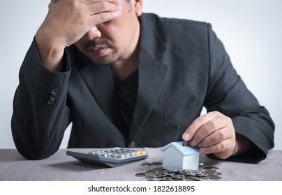 Businessman is putting coin into small house piggy bank, and feel stressed when they know that they do not have enough money to pay for home installments
