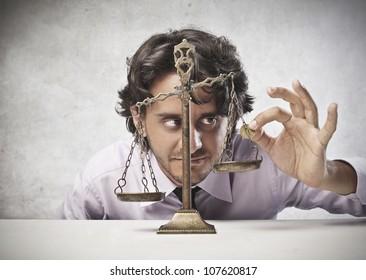 Businessman putting a coin on a balance