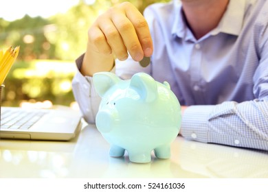 Businessman putting coin to the pig box. Laptop behind