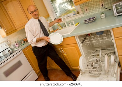 Businessman putting dishes into dishwasher
