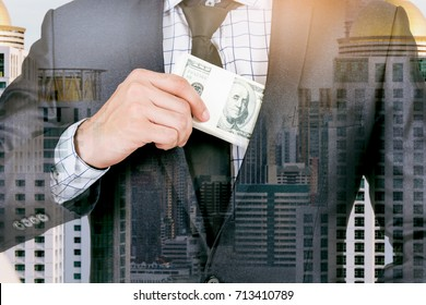 Businessman putting dollar banknotes into pocket