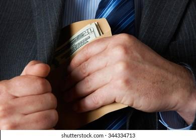 Businessman Putting Envelop of Dollars In Pocket