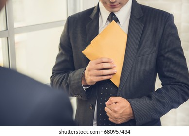 Businessman putting the envelope into his suit pocket - corruption and embezzlement concepts