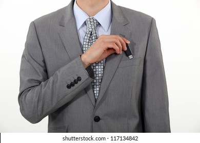 A businessman putting his Usb key in his pocket.