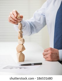 Businessman putting last block to the tower made of wooden blocks (Japanese game tumi-ishi), illustrating concept of business success, achievement and self-control