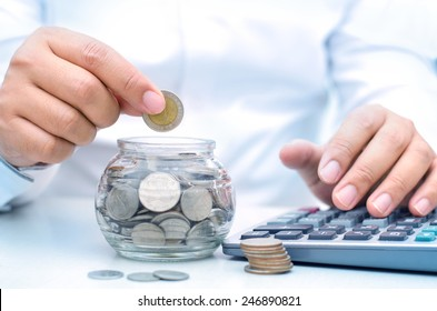 businessman putting money coins into glass jar bank for saving and insurance concept
