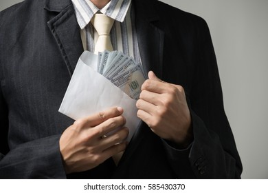 Businessman putting money in his pocket ,Photography in the studio in the corruption concept.