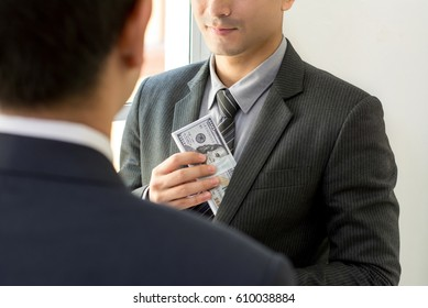 Businessman putting money into his suit pocket after making a deal with partner