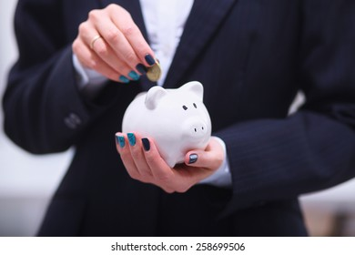 Businessman putting  money into a piggy bank isolated on white background