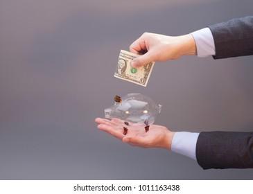 Businessman putting one dollar bill into glass piggy bank