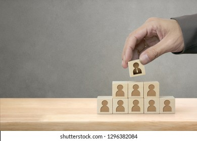 Businessman Putting Wood Cube Block on Top Pyramid with Copy Space, Management and Leadership Concept.
