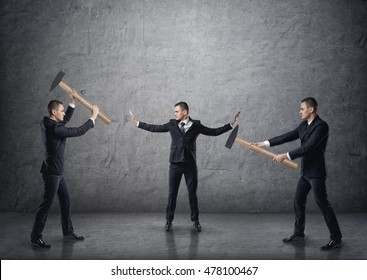 Businessman with raised hands separating two fighting businessmen with hammers. Conflicts and disputes. Collision and controversy. Pulling apart.