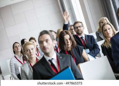 Businessman raising hand during seminar at convention center