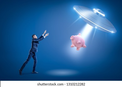A businessman raising hands toward a UFO which is pulling a piggy bank toward its open hatch by some invisible force. Close encounter. Attracting finances. Financial loss.