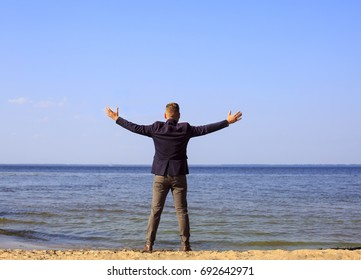 Businessman raising his arms, open palms, with face looking up to the sky - happy, success
