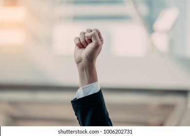 Businessman raising his fists in the air background business success, achievement, and win concepts.