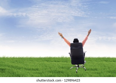 Businessman is raising his hands while sitting on his seat outdoor