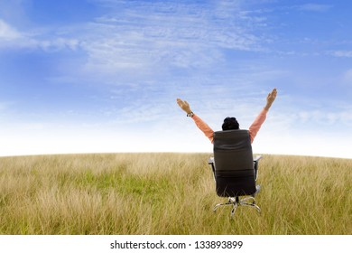 Businessman raising his hands while sitting on his seat in the field under blue sky