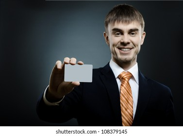 businessman  reach out on camera and show credit card or visiting card, smile