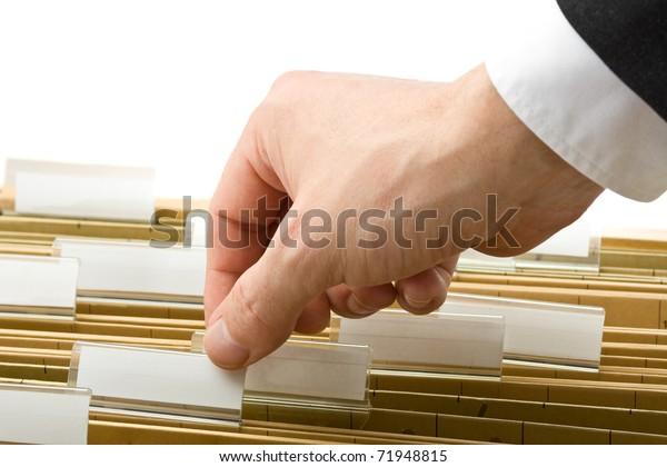 Businessman reaching for office folder in drawer