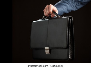 Businessman reaching out leather briefcase on black background