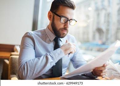 Businessman reading agreement before signing it