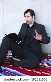 businessman reading a book outdoors and points with his finger that he doesnt want to be interrupted