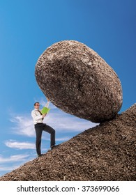 Businessman reading a book standing on slope blocking easily giant boulder with one hand from falling down