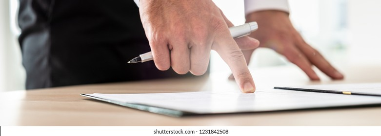 Businessman reading contract or document in folder pointing with his finger to an important part holding ink pen. With sun flare from the window through his fingers.