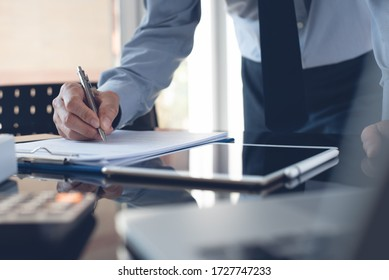 Businessman reading document before signing business contract or partnership agreement with digital tablet on desk. Corporate man, accountant working in modern office.