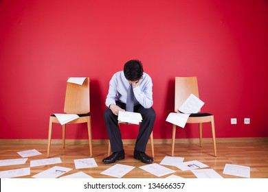 Businessman reading a document in a messy office full of papers on the floor