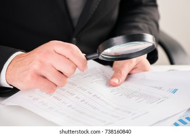 Businessman reading documents with magnifying glass concept for