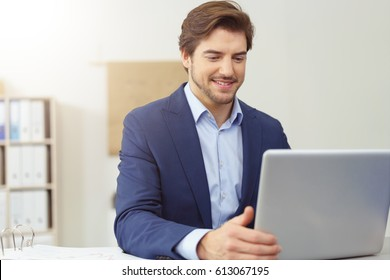 Businessman reading his laptop screen with a pleased smile of satisfaction as he sits at his desk in the office