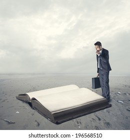 Businessman reading a huge old book in the desert.