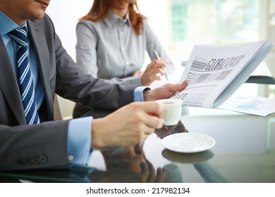 Businessman reading newspaper and having coffee in office