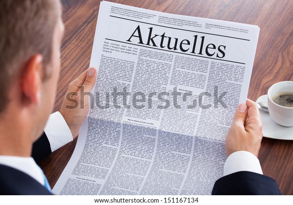Businessman Reading Newspaper With The Headline Current News