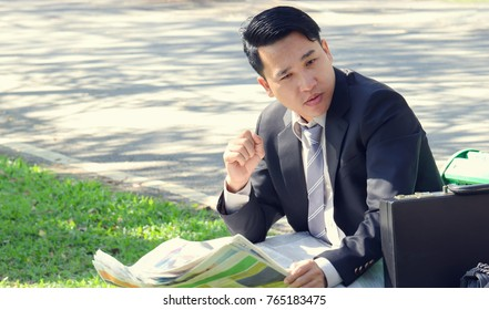 Businessman reading newspaper and looking for a new job sits in the public park. To communicate, plan and relax, change location. Use as background and design.